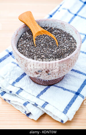 Nutritious chia seeds in ceramic bowl on wooden table for diet foods ingredients . Nutritious Foods and Super foods - Stock Photo