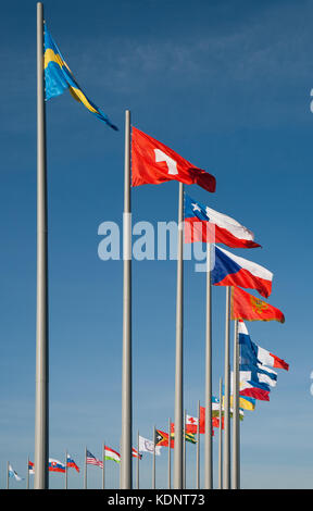 Flags of different countries against the background of blue sky - Stock Photo