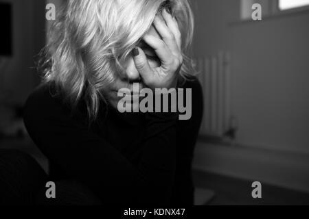 Woman holds her head in her hand.  Blonde woman in despair depressed tired. - Stock Photo