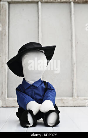 Little hand made Amish doll sitting against a rustic background - Stock Photo