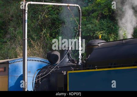 Steam train. Nilgiri mountain railway. Water refueling. Narrow-gauge. Historical locomotive - Stock Photo