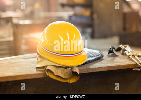 Yellow hardhat and old leather gloves - Stock Photo