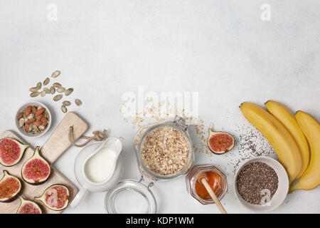 Ingredients for breakfast: oatmeal, milk, figs, bananas, chia seeds, honey, pumpkin seeds. view from above - Stock Photo
