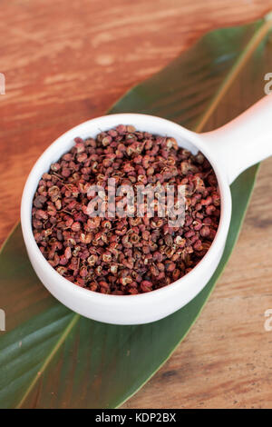 Sichuan peppercorns on white bowl over green leaf - Stock Photo