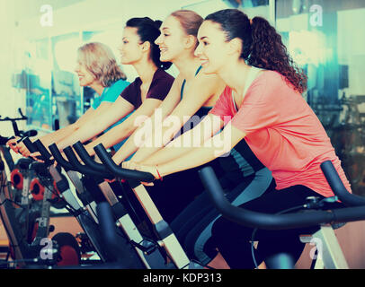 Women Of Different Age Training On Exercise Bikes Together Stock