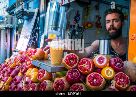 Street vendor sells Pomegranate juice at a stall in Istanbul Turkey - Stock Photo