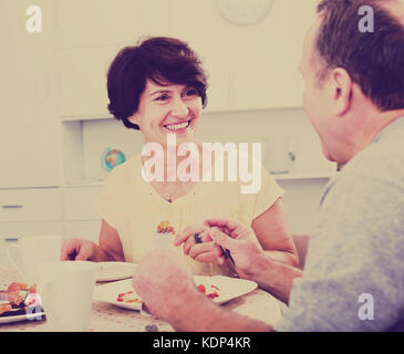 Cheerful mature woman eating lunch and listening to her husband at home - Stock Photo