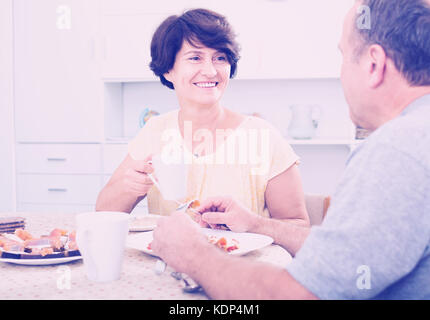 cheerful smiling senior woman enjoying her lunch and discussion with man at home - Stock Photo