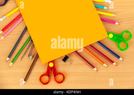 Sheet of orange card laying on top of colouring pencils and safety scissors on a wooden desk - Stock Photo