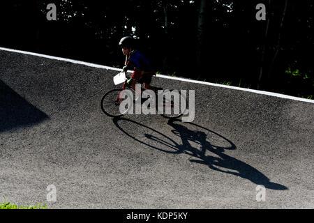 A little boy casting a long shadow on a BMX - Stock Photo