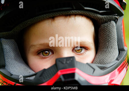 A portrait of a young boy (5 yrs old) wearing a full face cycle crash helmet - Stock Photo