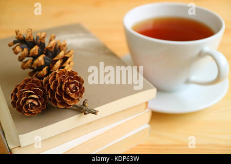 Cup of hot tea with dry pine cones on stack of books on natural color wooden table - Stock Photo