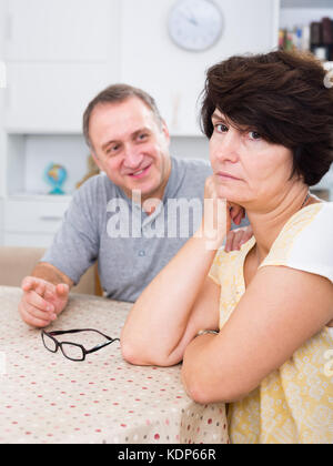 Sad adult woman experiencing family problems with partner indoors - Stock Photo
