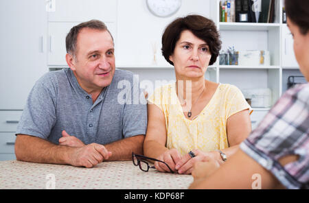 Serious mature couple having conversation with adult daughter at home - Stock Photo