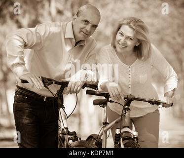 Elderly man and woman walking with bicycles on a summer weekend in the park - Stock Photo