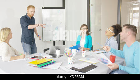 Young people in office sharing ideas - Stock Photo