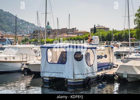 Como, Italy - May 27, 2016: The unrecognized girl in a recreation catamaran on the pier of Lake Como, Italy. - Stock Photo