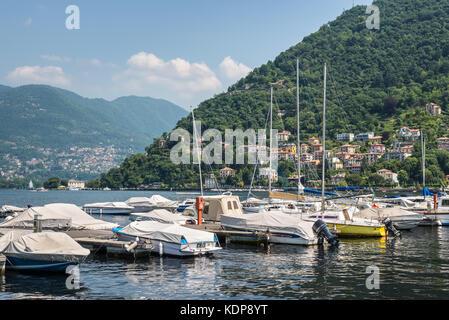 Como, Italy - May 27, 2016: Yachts and houses along Lake Como in city of Como, Italy. - Stock Photo
