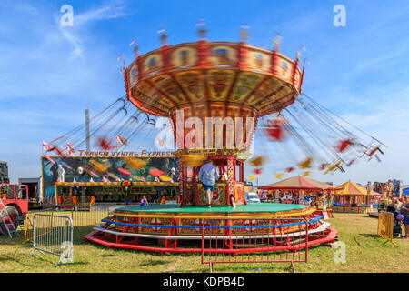 A chair swing ride carousel on a summers day England UK - Stock Photo