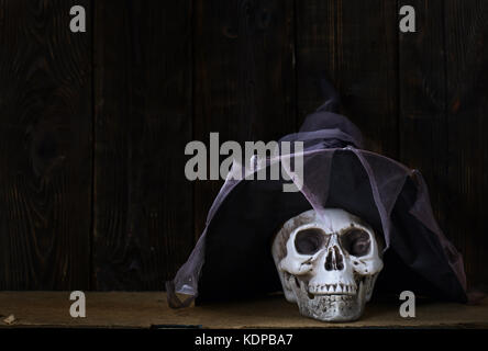 Human skull with magician hat at the wooden wall - Stock Photo