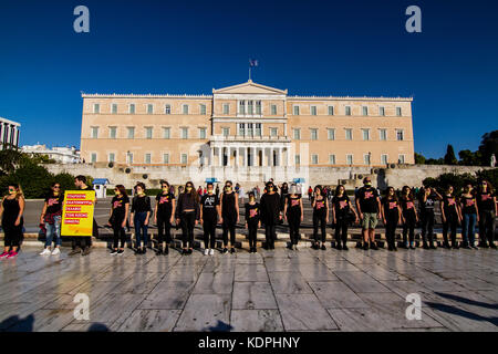 Protesters in front of the Parliament. Athenians march silently wearing black outfit and yellow ribbons on their - Stock Photo