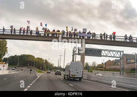 Runcorn. United Kingdom.  15 October. 2017. Protestors on a bridge over the access road for the New Mersey Gateway - Stock Photo