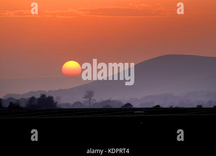 Glynde, East Sussex. 15th October 2017. The sun setting behind Mount Caburn, near Lewes, in the South Downs National - Stock Photo