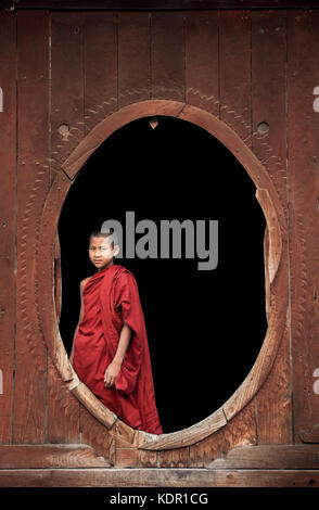 Myanmar, young novice Buddhist monks dressed in robes standing in wooden oval windows at Shwe Yaunghwe Kyaung Monastery - Stock Photo