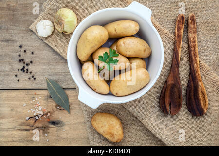Fresh organic potatoes in white ceramic bowl with ingredients and herbs , parsley, garlic, bay leaves, pepper, onion - Stock Photo