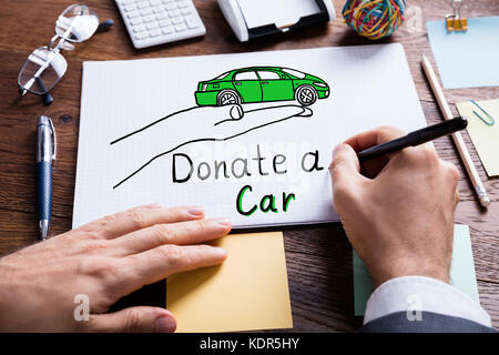 Close-up Of Businessperson Drawing Concept Of Car Donation On Notebook At Wooden Desk - Stock Photo