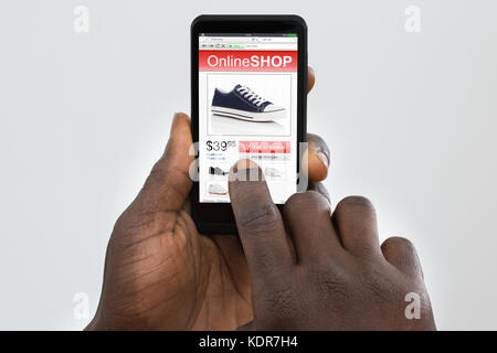Close-up Of Person Hand Shopping Online On Smartphone - Stock Photo