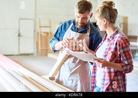Modern Carpenters Choosing Wood in Joinery - Stock Photo