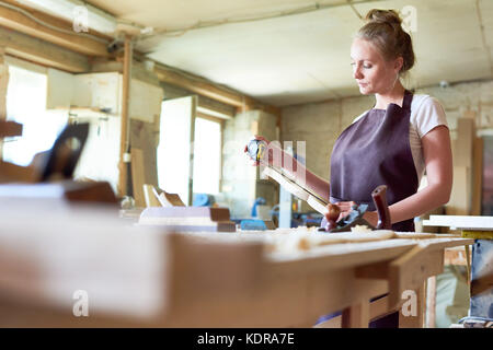 Female Carpenter Working in Shop - Stock Photo