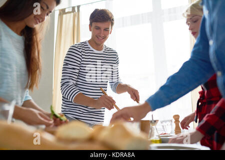 Young Man with Friends Setting Dinner Table - Stock Photo