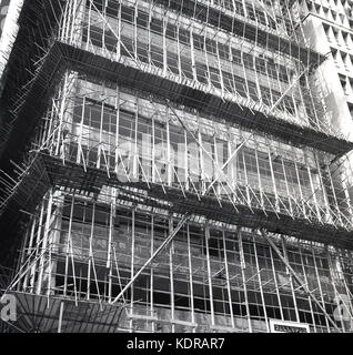 1950s, Hong Kong, Asia, historical picture showing the traditional wood, bamboo scaffolding commonly used for the - Stock Photo