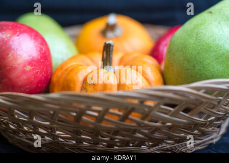fall harvest of apples,pears and pumpkins in a wicker basket. - Stock Photo