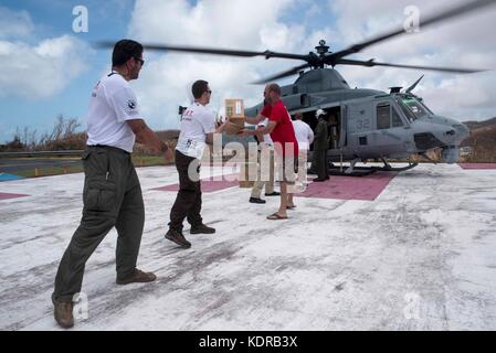 U.S. Marines and volunteers unload emergency supplies from a U.S. Marine Corps UH-1Y Venom Super Huey helicopter - Stock Photo