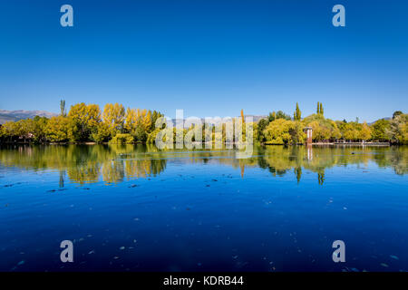 Autumn colors and reflection on Puigcerda's pond in Pyrenees. Located in north Catalonia, Spain. - Stock Photo