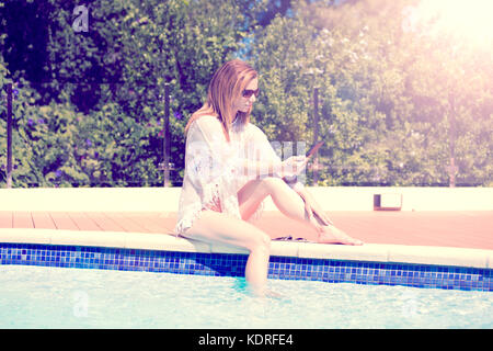 Europe, Spain, Balearen, Mallorca, in a garden of Canyamel -  a Young woman with long blond hair are sitting at - Stock Photo