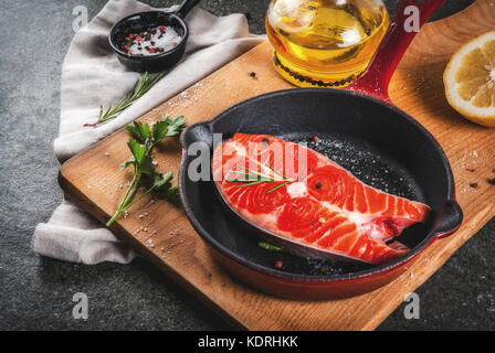 Raw fresh salmon fish with ingredients for cooking - olive oil, lemon, onion, parsley, rosemary, on frying pan, - Stock Photo