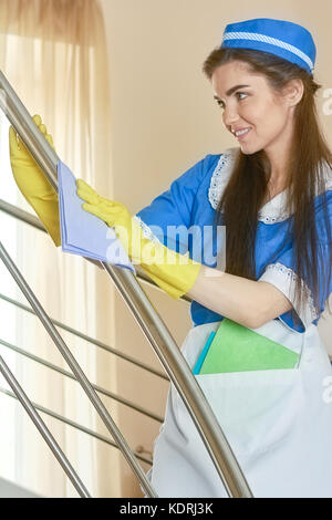 Housemaid in gloves working. - Stock Photo