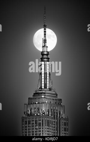 HOBOKEN, NJ - NOVEMBER 13, 2016: Full moon rises and aligns with the top of the Empire State Building. - Stock Photo