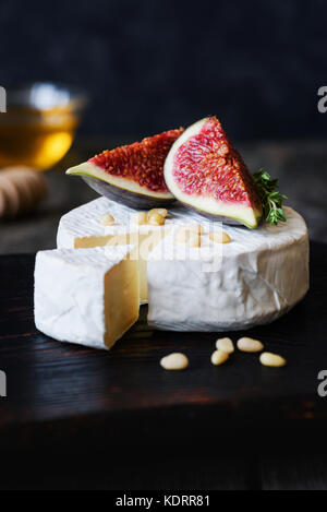 Brie, camambert cheese, fresh purple figs, nuts and honey on dark wooden backdrop. Closeup view, vertical - Stock Photo