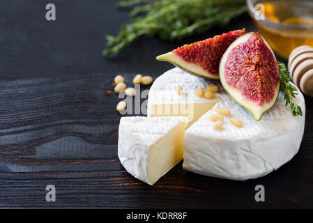 White cheese brie or camambert. Gourmet appetizer cheese plate with white cheese, figs, thyme, honey and nuts - Stock Photo