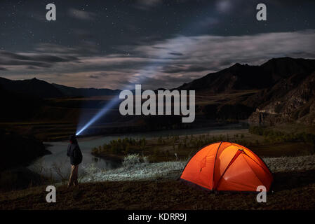 Male tourist with flashlight near his camp tent at night. - Stock Photo