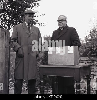 1960s, historical picture, two men, an elderly priest and a local  parishioner stand together outside with donation - Stock Photo
