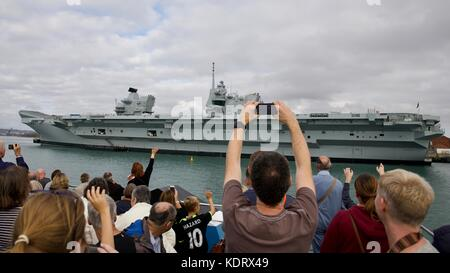 People taking photos of the Royal Navy flagship HMS Queen Elizabeth at Portsmouth Navel Base - Stock Photo