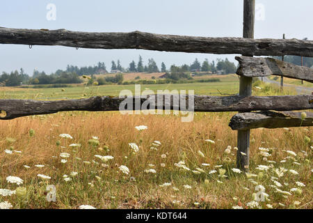 An old wooden fence in front of a pasture.  In the distance are a few homes and barns which are seen through the - Stock Photo