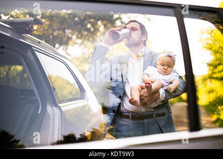 Young father carrying his baby girl. Man at the car, drinking coffee. Shot through glass. - Stock Photo