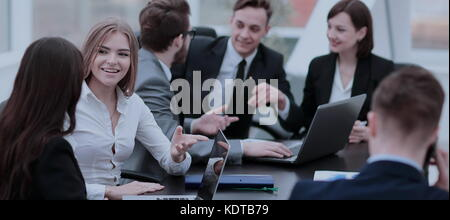 Smiling and confident business team working in front of a bright - Stock Photo